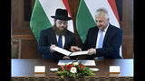 "Deputy prime minister in charge of Hungarian communities abroad, church policy and national and ethnic minorities, Zsolt Semjen, right, and Chief Rabbi of the Unified Israelite Congregation of Hungary (EMIH) Slomo Koves sign a comprehensive agreement at the Castle District premises of the Prime Minister's Office, in Budapest, Hungary, Monday, Nov. 18, 2019. By signing the agreement, the Hungarian state acknowledges the historical traditions of the Jewish community and ""EMIH's service to the renaissance of Hungary's Jewish community"", Semjen said at the signing ceremony."
