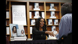 """Former first lady Michelle Obama greets people as they buy signed copies of her book, """"Becoming,"""" Monday Nov. 18, 2019, at Politics and Prose Bookstore in Washington. (AP Photo/Jacquelyn Martin)"""