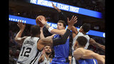 Dallas Mavericks forward Luka Doncic (77) puts up a shot against San Antonio Spurs center LaMarcus Aldridge (12) and San Antonio Spurs guard Dejounte Murray (5) in the first half of an NBA basketball game Monday, Nov. 18, 2019, in Dallas. (AP Photo/Richard W. Rodriguez)