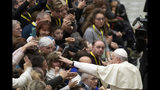 Pope Francis salutes faithful in the Paul VI Hall at the Vatican at the end of an audience with members of parish evangelization services, Monday, Nov. 18, 2019. (AP Photo/Alessandra Tarantino)