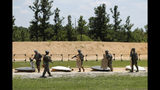 Soldiers prepare to leave a firing range at Fort Bragg in North Carolina on Tuesday, July 30, 2019. The area where guns are fired and bombs are detonated is ideal habitat for the rare St. Francis' satyr butterfly. (AP Photo/Robert F. Bukaty)