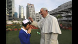 A nurse bows to the life size statue of Pope Francis as her friend takes a photograph at the St.Louis hospital in Bangkok, Thailand, Tuesday, Nov. 19, 2019. Pope Francis arrives in Thailand on Wednesday for the first visit here by the head of the Roman Catholic Church since St. John Paul II in 1984. (AP Photo/Manish Swarup)