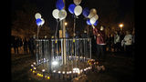 Jessica Dumont, a former student at Saugus High School, places balloons on a makeshift memorial at Central Park in honor of the victims of a shooting at the high school Thursday, Nov. 14, 2019, in Santa Clarita, Calif. Los Angeles County sheriff's officials say a 16-year-old student shot several classmates and then himself in a quad area of Saugus High School Thursday morning. (AP Photo/Marcio Jose Sanchez)