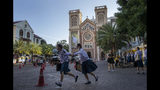 School children run in the courtyard of Assumption Cathedral, decorated with posters of Pope Francis in Bangkok, Thailand, Wednesday, Nov. 20, 2019. Pope Francis arrives in Thailand on Wednesday for the first visit here by the head of the Roman Catholic Church since St. John Paul II in 1984. (AP Photo/Gemunu Amarasinghe)