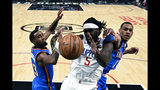 Los Angeles Clippers' Montrezl Harrell (5) fights for a rebound against Oklahoma City Thunder's Terrance Ferguson (23) and Darius Bazley (7) during the first half of an NBA basketball game, Monday, Nov. 18, 2019, in Los Angeles. (AP Photo/Ringo H.W. Chiu)