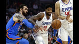 Los Angeles Clippers' Paul George (13) and Oklahoma City Thunder's Steven Adams (12) fight for a ball during the first half of an NBA basketball game, Monday, Nov. 18, 2019, in Los Angeles. (AP Photo/Ringo H.W. Chiu)