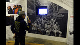 In this photo taken Tuesday, Nov. 12, 2019, Eloy Martinez, who took part in the Native American occupation of Alcatraz 50 years earlier, looks over a group photograph showing the occupiers displayed in an exhibit on the island in San Francisco. The week of Nov. 18, 2019, marks 50 years since the beginning of a months-long Native American occupation at Alcatraz Island in the San Francisco Bay. The demonstration by dozens of tribal members had lasting effects for tribes, raising awareness of life on and off reservations, galvanizing activists and spurring a shift in federal policy toward self-determination. (AP Photo/Eric Risberg)