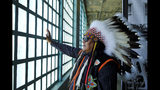 Jason Morsette, of New Town, North Dakota, looks out toward the bay and the Golden Gate Bridge through barred windows during ceremonies for the 50th anniversary of the Native American occupation of Alcatraz Island Wednesday, Nov. 20, 2019, in San Francisco. About 150 people gathered at Alcatraz to mark the 50th anniversary of a takeover of the island by Native American activists. Original occupiers, friends, family and others assembled Wednesday morning for a program that included prayer, songs and speakers. They then headed to the dock to begin restoring messages painted by occupiers on a former barracks building. (AP Photo/Eric Risberg)