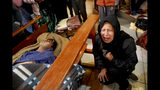 Gloria Quispe mourns next to the body of her brother Antonio, killed during clashes between security forces and supporters of former President Evo Morales, at the San Francisco de Asis church in El Alto, outskirts of La Paz, Bolivia, Wednesday, Nov. 20, 2019. Police and soldiers on Tuesday escorted gasoline tankers from a major fuel plant that had been blockaded for five days by Morales' backers and at least three people were reported killed while the operation was underway. (AP Photo/Natacha Pisarenko)