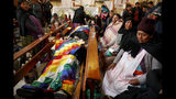 Relatives mourn next to the bodies of people killed during clashes between security forces and supporters of former President Evo Morales, at the San Francisco de Asis church in El Alto, outskirts of La Paz, Bolivia, Wednesday, Nov. 20, 2019. Police and soldiers on Tuesday escorted gasoline tankers from a major fuel plant that had been blockaded for five days by Morales' backers and at least three people were reported killed while the operation was underway. (AP Photo/Natacha Pisarenko)