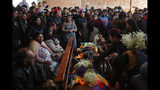 Mourners gather around the bodies of people killed during clashes between security forces and supporters of former President Evo Morales, at the San Francisco de Asis church in El Alto, outskirts of La Paz, Bolivia, Wednesday, Nov. 20, 2019. Police and soldiers on Tuesday escorted gasoline tankers from a major fuel plant that had been blockaded for five days by Morales' backers and at least three people were reported killed while the operation was underway. (AP Photo/Natacha Pisarenko)