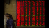 In this Tuesday, Nov. 19, 2019 photo, Chinese investors use computer terminals as they monitor stock prices at a brokerage house in Beijing. Shares retreated in Asia on Wednesday after Japan reported its worst monthly decline in exports in three years. (AP Photo/Mark Schiefelbein)