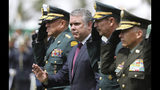 FILE - In this Nov. 7, 2019 file photo, Colombia's President Ivan Duque waves to police cadets, accompanied by his interim Defense Minister and Armed Forces Commander Gen. Luis Fernando Navarro, left, during a graduation ceremony for the cadets in Bogota, Colombia. Labor unions, student groups and ordinary citizens are expected to join in on Thursday, Nov. 21, in what could be one of the nation's biggest demonstrations in recent years, testing the Duque government as unrest grips the region. (AP Photo/Fernando Vergara, File)