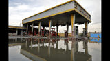 A gas station that was attacked during protests over rises in government-set gasoline prices is reflected in a puddle, in Tehran, Iran, Wednesday, Nov. 20, 2019. Demonstrations struck at least 100 cities and towns, spiraling into violence that saw banks, stores and police stations attacked and burned. (AP Photo/Ebrahim Noroozi)