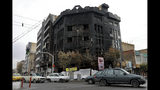 Traffic passes a building set ablaze during recent protests over government-set gasoline prices rises, in Tehran, Iran, Wednesday, Nov. 20, 2019. The demonstrations struck at least 100 cities and towns, spiraling into violence that saw banks, stores and police stations attacked and burned. (AP Photo/Ebrahim Noroozi)