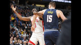 Houston Rockets guard James Harden, left, is hooked by Denver Nuggets center Nikola Jokic while driving to the rim in the first half of an NBA basketball game Wednesday, Nov. 20, 2019, in Denver. (AP Photo/David Zalubowski)