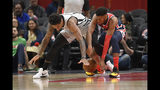 San Antonio Spurs guard DeMar DeRozan, left, and Washington Wizards guard Troy Brown Jr. reach for the ball during the first half of an NBA basketball game Wednesday, Nov. 20, 2019, in Washington. (AP Photo/Nick Wass)