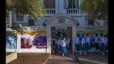 School children walk at Assumption convent, decorated with posters of Pope Francis in Bangkok, Thailand, Wednesday, Nov. 20, 2019. Pope Francis arrives in Thailand on Wednesday for the first visit here by the head of the Roman Catholic Church since St. John Paul II in 1984. (AP Photo/Gemunu Amarasinghe)