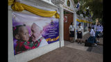 School children greet their teachers at Assumption convent, decorated with posters of Pope Francis in Bangkok, Thailand, Wednesday, Nov. 20, 2019. Pope Francis arrives in Thailand on Wednesday for the first visit here by the head of the Roman Catholic Church since St. John Paul II in 1984. (AP Photo/Gemunu Amarasinghe)