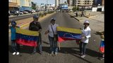 In this Nov. 16, 2019 photo, anti-government protestors block a road during a nationwide demonstration in Maracaibo, Venezuela. Opposition leader Juan Guaido, who seeks to oust President Nicolas Maduro, has urged Venezuelans to take to the streets, trying to reignite a movement started early this year. However, few in Maracaibo have responded, despite it being a city hard hit by crisis. (AP Photo/Rodrigo Abd)