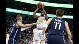 Dallas Mavericks forward Kristaps Porzingis (6) and forward Luka Doncic (77) defend as Golden State Warriors forward Glenn Robinson III (22) attempts a shot in the first half of an NBA basketball game in Dallas, Wednesday, Nov. 20, 2019. (AP Photo/Tony Gutierrez)