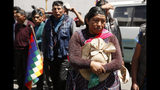 A woman takes part in a funeral procession for people killed in clashes between supporters of former President Evo Morales and security forces, in La Paz, Bolivia, Thursday, Nov. 21, 2019. At least eight people were killed Tuesday when security forces cleared a blockade of a fuel plant by Morales's backers in the city of El Alto. (AP Photo/Natacha Pisarenko)