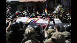 Mourners and anti-government demonstrators carry a coffin that contain the remains of a person killed in clashes between supporters of former President Evo Morales and security forces, in a funeral procession into La Paz, Bolivia, Thursday, Nov. 21, 2019. In an attempt to curb the social upheaval in Bolivia, interim President Jeanine Anez sent a bill to Congress to call for new elections amid an escalation of violence that has left 30 people dead. (AP Photo/Natacha Pisarenko)
