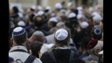 FILE - In this Wednesday, April 25, 2018 file photo people wear Jewish skullcaps, or kippa, as they attend a demonstration against an anti-Semitic attack in Berlin, Germany. A new survey says about one in four Europeans hold anti-Semitic beliefs, with such attitudes on the rise in eastern countries and mostly steady in the west. (AP Photo/Markus Schreiber, file)