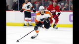 Philadelphia Flyers' Sean Couturier (14) gets ready to shoot the puck after taking it past Carolina Hurricanes' Dougie Hamilton (19) during the first period of an NHL hockey game in Raleigh, N.C., Thursday, Nov. 21, 2019. (AP Photo/Karl B DeBlaker)