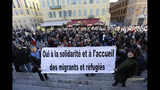 """This Jan. 4, 2017 photo shows a crowd supporting Cedric Herrou, a French activist farmer accused of helping African migrants to cross the border from Italy, in Nice, southern France. The banner reads """"Yes to solidarity and Welcome migrants and refugees"""". A French appeals court is expected to hand down a verdict Thursday afternoon in the case of a mountain guide who was convicted for helping migrants enter the country illegally.(AP Photo/Claude Paris, File)"""