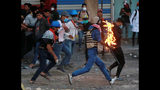 Demonstrators try to extinguish a protester who has caught fire, during clashes between Iraqi security forces and anti-Government protesters, in Baghdad, Iraq, Thursday, Nov. 21, 2019. Iraqi officials said several protesters were killed as heavy clashes erupt in central Baghdad. (AP Photo/Khalid Mohammed)