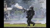A police officer fires tear gas at anti-government protesters in Bogota, Colombia, Thursday, Nov. 21, 2019. Colombia's main union groups and student activists called for a strike to protest the economic policies of Colombian President Ivan Duque government and a long list of grievances. (AP Photo/Ivan Valencia)