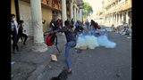 Riot police fire tear gas during clashes with anti-government demonstrators in Baghdad, Iraq, Friday, Nov. 22, 2019. Iraq's massive anti-government protest movement erupted Oct. 1 and quickly escalated into calls to sweep aside Iraq's sectarian system. Protesters occupy several Baghdad squares and parts of three bridges in a standoff with security forces. (AP Photo/Hadi Mizban)