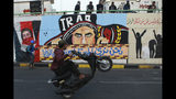 In this Sunday, Nov. 17, 2019 photo, a protestor races his motorbike past graffiti in the Saadoun Tunnel, in Baghdad, Iraq. The underpass running beneath Baghdad's Tahrir Square has become an ad hoc museum chronicling Iraq's massive anti-government protests. Young protesters have covered the walls of Saadoun Tunnel with images and murals that illustrate the country's tortured past, and the Iraq they aspire to. (AP Photo/Hadi Mizban)
