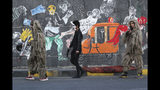 In this Sunday, Nov. 17, 2019 photo, protesters wear camouflage sniper uniforms and hold toy guns as they pass by graffiti at the Saadoun Tunnel, in Baghdad, Iraq. The tunnel that passes under Baghdad's landmark Tahrir Square has become an ad hoc museum for Iraq's revolution: Young artists draw images and murals that illustrate the country's tortured past, and the Iraq they aspire to. (AP Photo/Hadi Mizban)