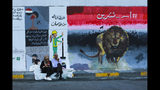 """In this Sunday, Nov. 17, 2019 photo, people sit near graffiti in the Saadoun tunnel, in Baghdad, Iraq. The tunnel that passes under Baghdad's landmark Tahrir Square has become an ad hoc museum for Iraq's revolution: Young artists draw images and murals that illustrate the country's tortured past, and the Iraq they aspire to. Messages in Arabic, include, """"Lion of October, Clean is from belief, They give us corruption, we give them a revolution and A revolution mixed with crude oil will not quell."""" (AP Photo/Hadi Mizban)"""