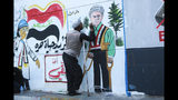 In this Sunday, Nov. 17, 2019 photo, a protestor adds some details and facial expressions to graffiti that was drawn by an Iraqi artist, at the Saadoun Tunnel, in Baghdad, Iraq. The tunnel that passes under Baghdad's landmark Tahrir Square has become an ad hoc museum for Iraq's revolution: Young artists draw images and murals that illustrate the country's tortured past, and the Iraq they aspire to. (AP Photo/Hadi Mizban)