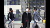 In this Thursday, Nov. 21, 2019, photo, people walk in front of an electronic stock board of a securities firm in Tokyo. Stocks logged modest gains Friday, Nov. 22, 2019, in Asia after a lackluster overnight session on Wall Street ended with the market's third straight drop. (AP Photo/Koji Sasahara)