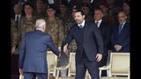 Former Prime Minister Saad Hariri, right, shakes hands with Lebanese Parliament Speaker Nabih Berri as attend a military parade to mark the 76th anniversary of Lebanon's independence from France at the Lebanese Defense Ministry, in Yarzeh near Beirut, Lebanon, Friday, Nov. 22, 2019. Lebanon's top politicians Friday, attended a military parade on the country's 76th Independence Day, appearing for the first time since the government resigned amid nationwide protests now in their second month. (AP Photo/Hassan Ammar)