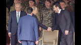 Lebanese President Michel Aoun, center, shakes hands with former Prime Minister Saad Hariri, right, and Parliament Speaker Nabih Berri, before a military parade to mark the 76th anniversary of Lebanon's independence from France at the Lebanese Defense Ministry, in Yarzeh near Beirut, Lebanon, Friday, Nov. 22, 2019. Lebanon's top politicians attended Friday a military parade on the country's 76th Independence Day, appearing for the first time since the government resigned amid nationwide protests now in their second month. (AP Photo/Hassan Ammar)