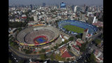 The Plaza de Toros Mexico bullring, left, that has been transformed to host an upcoming exhibition tennis match between Swiss great Roger Federer and German rival Alexander Zverev, sits next to the Estadio Azul soccer stadium, in Mexico City, Friday, Nov. 22, 2019. For 73 years, Plaza de Toros Mexico has been witness to mostly great bullfights and mighty matadors, but it as also hosted motocross events, concerts, as well as wrestling and boxing matches. (AP Photo/Rebecca Blackwell)