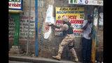 En esta imagen, tomada el 18 de noviembre de 2019, un agente de policía apunta su arma a residentes del distrito Delmas 95 durante una protesta para exigir la renuncia del presidente, Jovenel Moise, en Puerto Príncipe, Haití. Al menos cuatro personas resultaron heridas por disparos durante una pequeña protesta en la capital haitiana luego de un discurso del cuestionado Moise. (AP Foto/Dieu Nalio Chery)