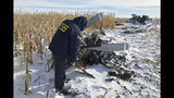 In this Monday, Dec. 2, 2019, photo provided by the National Transportation Safety Board (NTSB), an NTSB air safety investigator begins the initial examination of the wreckage of the Pilatus PC-12 that crashed in Chamberlain, S.D., on Nov. 30, 2019, shortly after departure from Chamberlain Municipal Airport. (NTSB via AP)