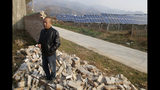 In this Nov. 28, 2019, photo, Chan Shicun, a construction materials trader, points to a wall he said local authorities destroyed after a disagreement with a massive government-backed solar project in Ruicheng County in central China's Shanxi Province. As world leaders gather in Madrid to discuss how to slow the warming of the planet, a spotlight is falling on China, the top emitter of greenhouse gases. China burns about half the coal used globally each year. Yet it's also the leading market for solar panels, wind turbines and electric vehicles. (AP Photo/Sam McNeil)