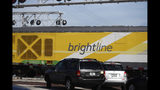 Vehicles wait for a Brightline passenger train to pass on Wednesday, Nov. 27, 2019, in Oakland Park, Fla. After Richard Branson announced his Virgin Group would partner with Brightline, Florida's new higher-speed passenger rail service, a train whisked the British billionaire, VIPs and journalists from Miami to West Palm Beach in just over an hour and then back, with no problems. (AP Photo/Brynn Anderson)
