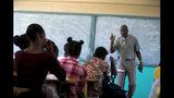 Jean-Marc Charles, director de una secundaria, da clases en un aula en Petion-Ville, Haití, el jueves 28 de noviembre de 2019, después de que algunos planteles reanudaran clases tras meses de violentos disturbios. (AP Foto/Dieu Nalio Chery)