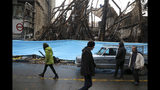 FILE - In this Nov. 20, 2019, file photo, people walk past buildings that were burned during recent protests, in Shahriar, Iran, some 40 kilometers (25 miles) southwest of the capital, Tehran. Amnesty International says at least 208 people in Iran have been killed amid protests over sharply rising gasoline prices and a subsequent crackdown by security forces. The country has yet to release any nationwide statistics about the unrest last month. (AP Photo/Vahid Salemi, File)