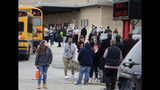 Waukesha South High School students find their waiting parents and friends and hug after they leave the building following shots fired inside the school, Monday, December 2, 2019. A suspect is in custody after a student exchanged gunfire with a school resource officer Monday morning, a spokeswoman for the school district confirmed. (Rick Wood/Milwaukee Journal-Sentinel via AP)