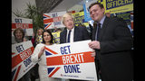 Home Secretary Priti Patel, center left, Britain's Prime Minister Boris Johnson, center, and MP Will Quince pose holding a sign before a rally event as part of the General Election campaign, in Colchester, England, Monday, Dec. 2, 2019. British Prime Minister Boris Johnson and main opposition Labour Party leader Jeremy Corbyn paused to honor the two people killed in the London Bridge attack, then went back to trading blame for the security failings that allowed a man who had been jailed for terrorist crimes to go on a violent rampage in the heart of London. (Hannah McKay/Pool Photo via AP)