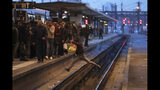 FILE - In this Tuesday, April 3, 2018 file photo a passenger crosses railroad tracks at rush hour at Gare de Lyon train station, in Paris. France's rail operator SNCF and the Paris Metro say nationwide strikes will wipe out most services Thursday, impacting millions. The SNCF expects that 9 out of 10 high-speed trains won't run and that half of the Eurostar services linking France and Britain will be canceled, too. (AP Photo/Francois Mori, File)